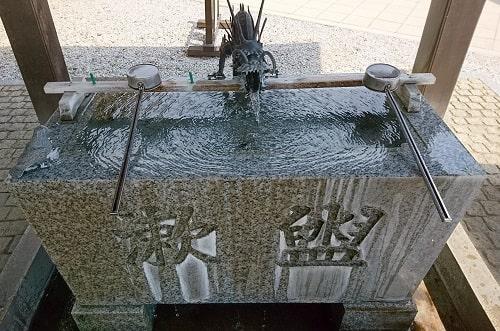 鳩の石の像がいる手水舎の風景