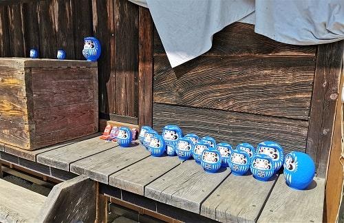 拝殿横に奉納されている青いだるまの風景