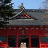 森林の中にひときわ目立つ朱色の赤城神社本殿の景色