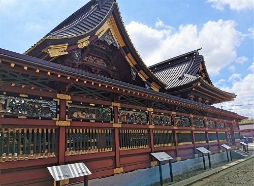 社殿の横の彫刻と本殿の風景