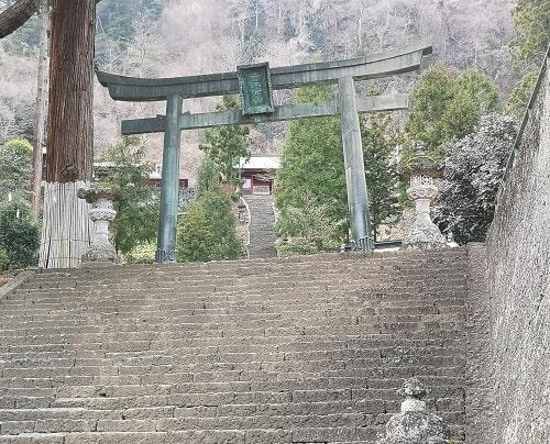 石段の上にそびえ立つ銅鳥居の風景