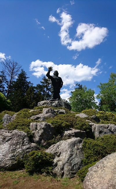 青空の下にそびえ立つ日本武尊の銅像風景