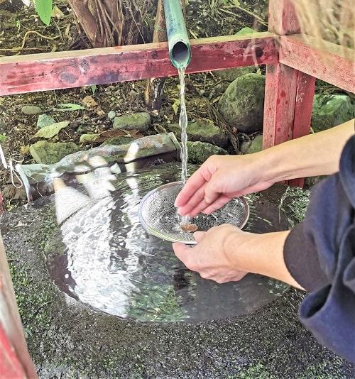銭洗所で500円玉を洗っている風景