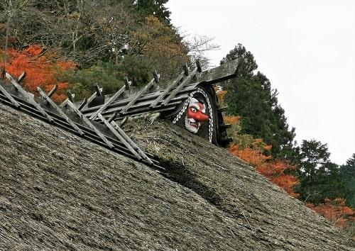 茅葺屋根に掲げられている天狗のお面の風景