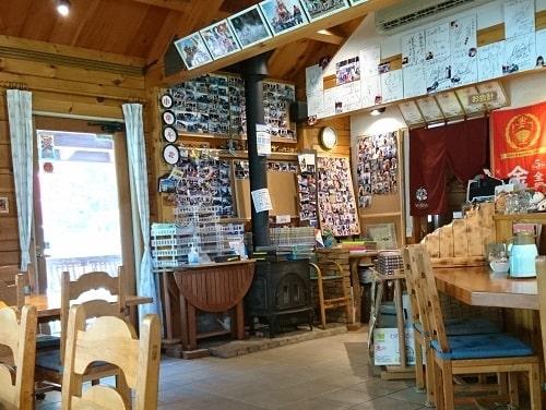 たぬ金亭の入り口に来店したライダーたちの写真が貼られているのわかる画像