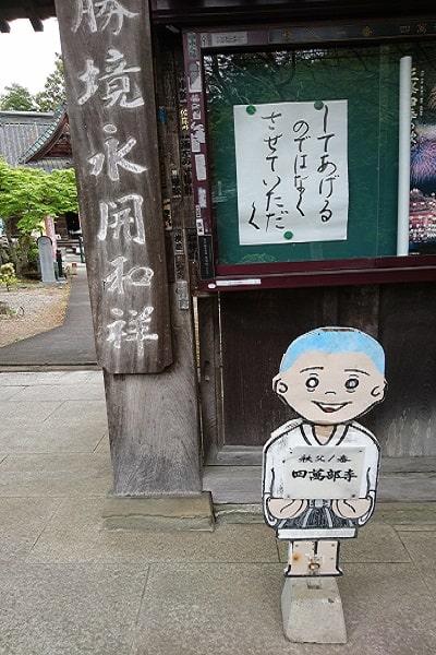 お寺の入り口で出迎えてくれている立て看板の小坊主さん