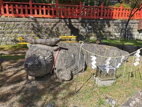 牛が寝そべっている姿をした石がある風景